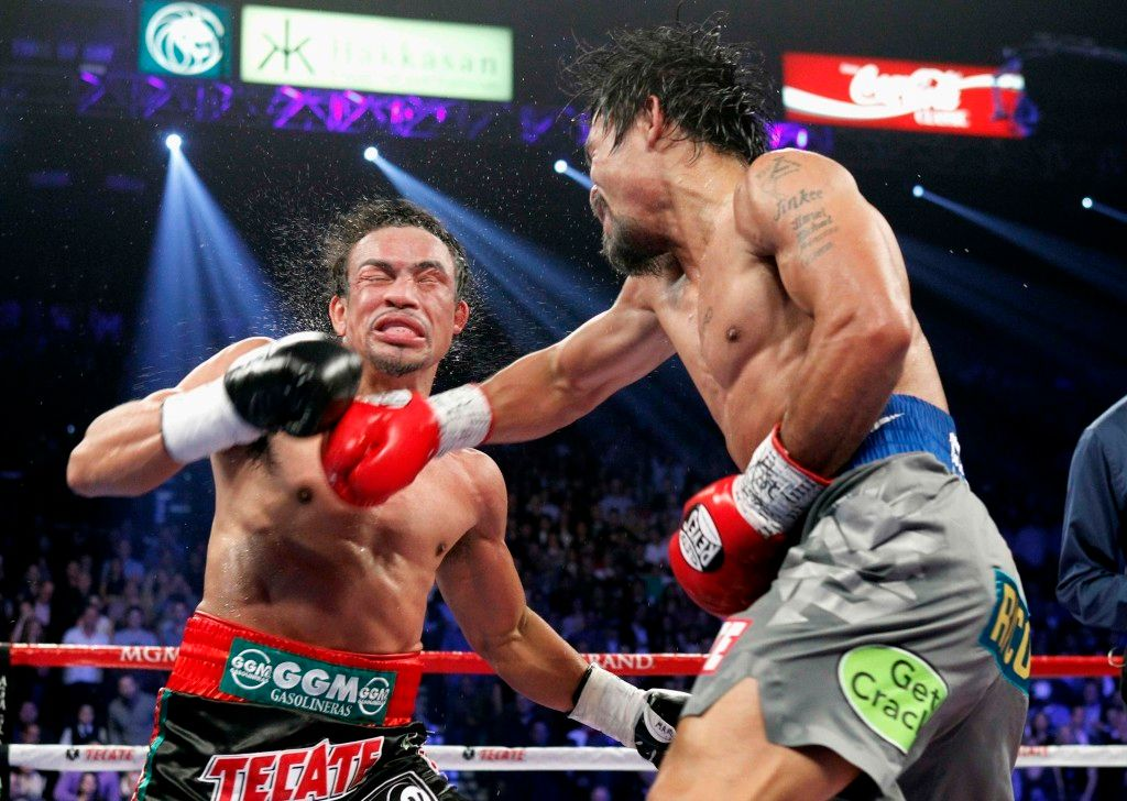 Juan Manuel Marquez of Mexico takes a punch from Manny Pacquiao of the Philippines during their welterweight fight at the MGM Grand Garden Arena in Las Vegas