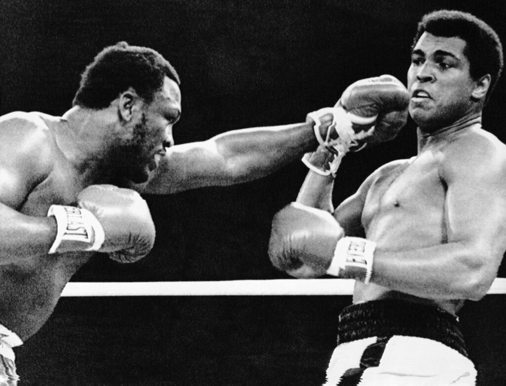 01 Oct 1975, Manila, Philippines --- Joe Frazier reaches out with a left as Muhammad Ali pulls back during the first round of their 15-round title fight. Later Frazier suffers a TKO in the 14th round and Ali remains the middleweight champion of the world. --- Image by © Bettmann/CORBIS