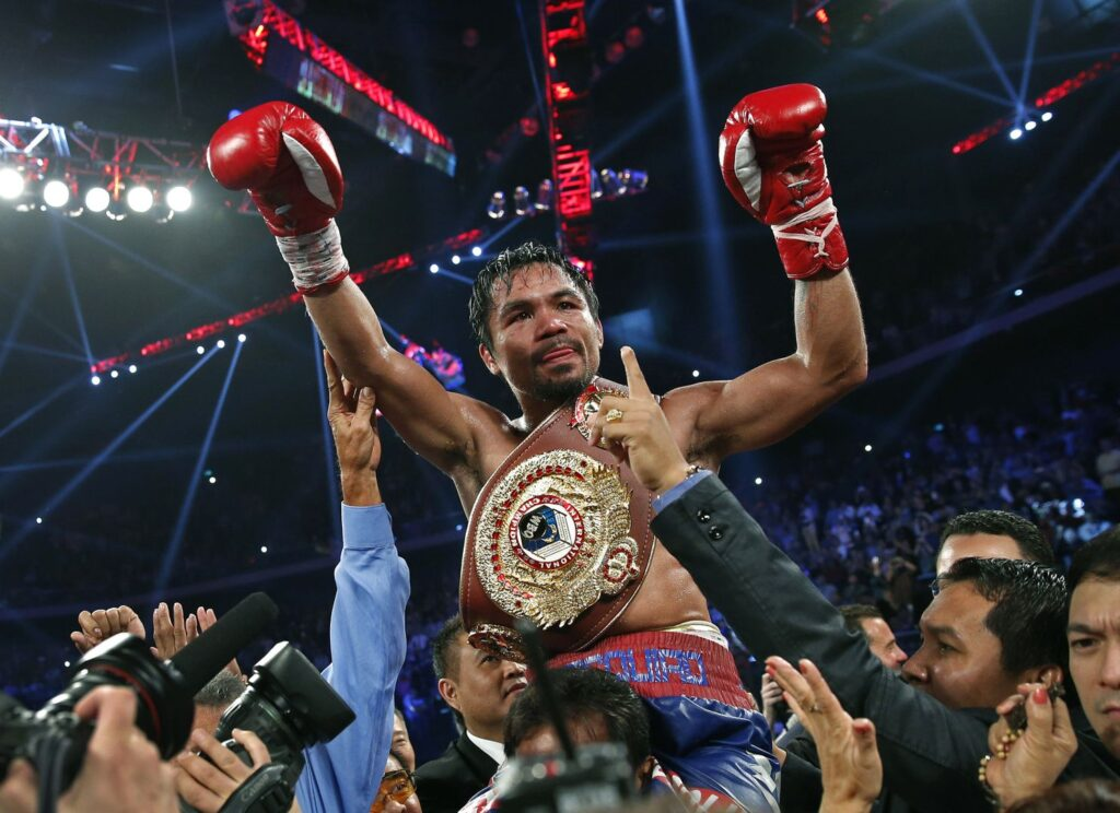 Manny Pacquiao from the Philippines wears the champion's belt after defeating Brandon Rios of the United States in their WBO international welterweight title fight Sunday, Nov. 24, 2013, in Macau. Pacquiao defeated Rios by unanimous decision on Sunday to take the WBO international welterweight title and return to his accustomed winning ways after successive defeats. (AP Photo/Vincent Yu)