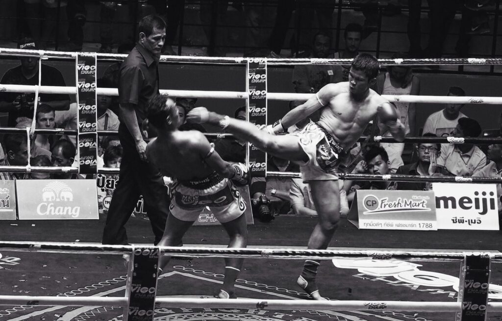 Saenchai leaning back to dodge a kick from fellow Muay Thai legend Nong-O Gaiyanghadaogym.