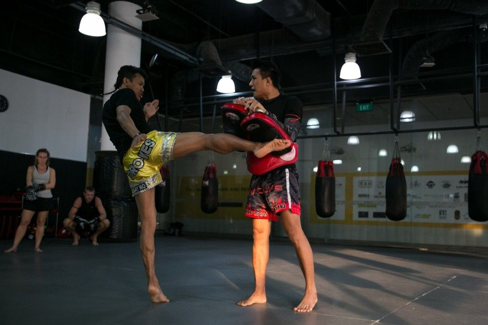 Multiple-time Muay Thai World Champion Orono Wor Petchpun demonstrates a right kick with multiple-time Lumpinee Muay Thai World Champion Namsaknoi Yudthagarngamtorn.