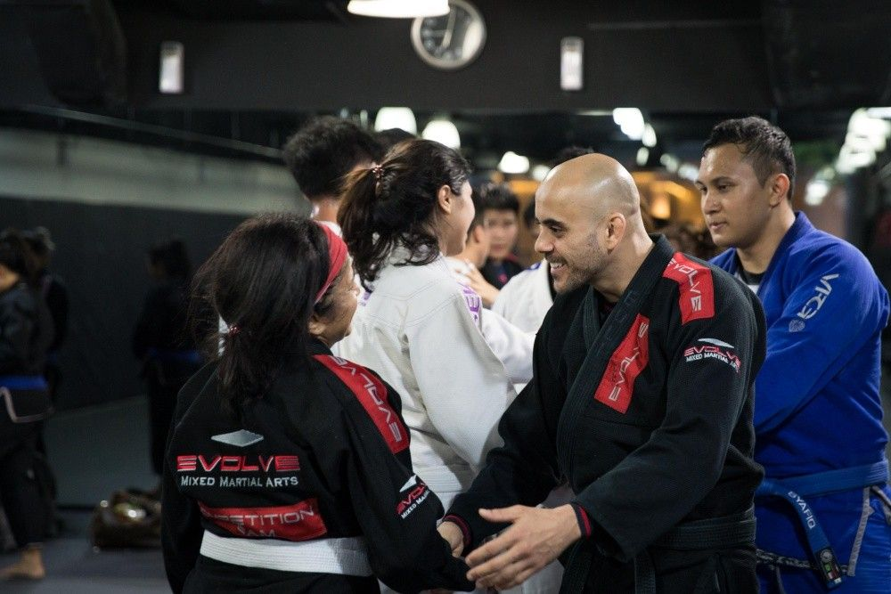 "BJJ Champion Thiago ""Guli"" Kozama congratulates a student after another challenging BJJ class."