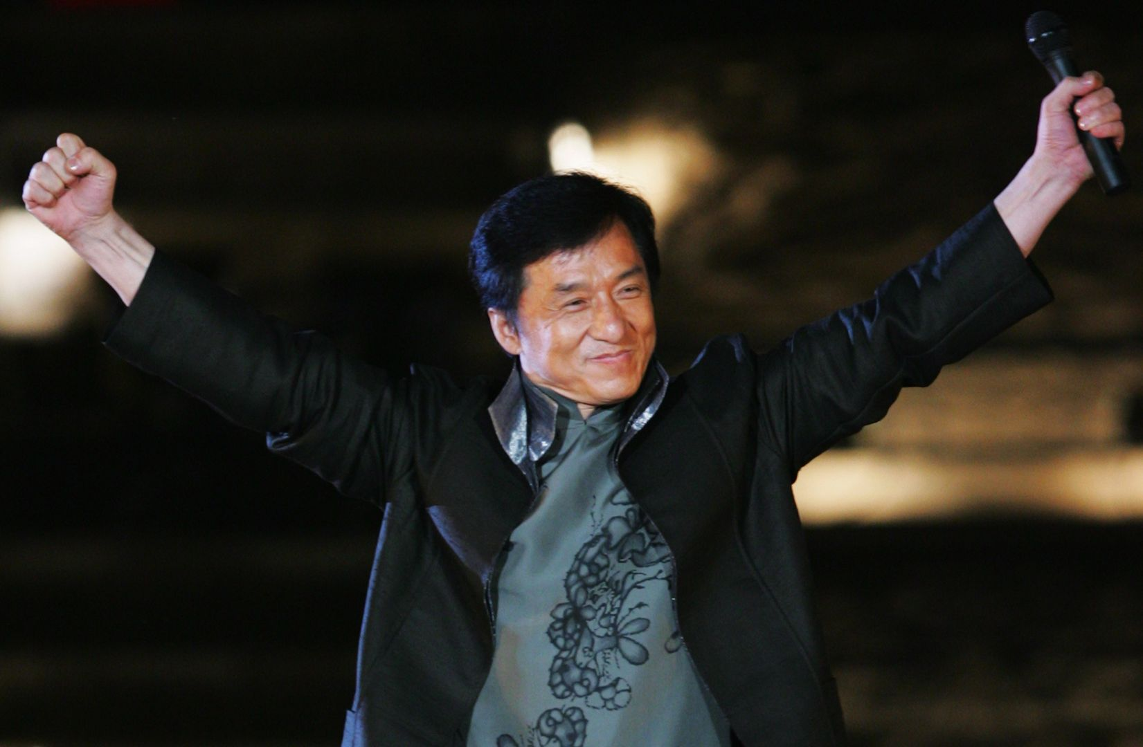 BEIJING - APRIL 30: Hong Kong's star Jackie Chan performs during the Award-giving Ceremony for the fourtth Olympic Songs Competition at the illuminated Worker People's Cultural Palace, the Imperial Ancestral Temple inside the Forbidden City, on April 30, 2008 in Beijing, China. Various activities, including an international long distance race, a song festival, a grand evening and an international speed-walking race, will be held in Beijing to celebrate the 100-day mark which falls on April 30. (Photo by Feng Li/Getty Images)