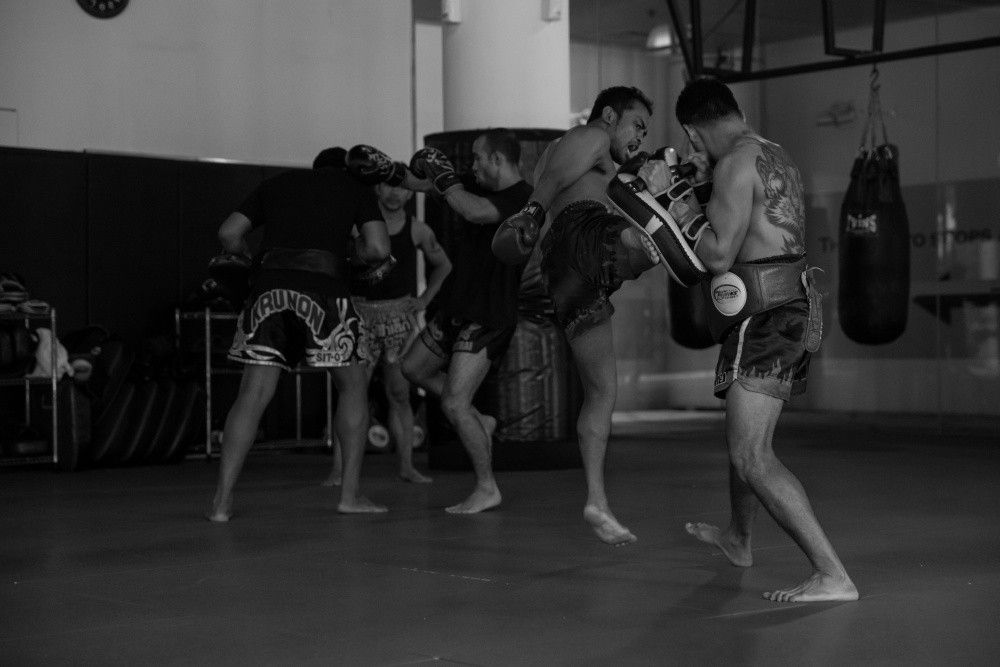 Multiple-time Muay Thai World Champions Dejdamrong Sor Amnuaysirichoke and Pornsanae Sitmonchai help each other out at the Evolve MMA Fighters Program.