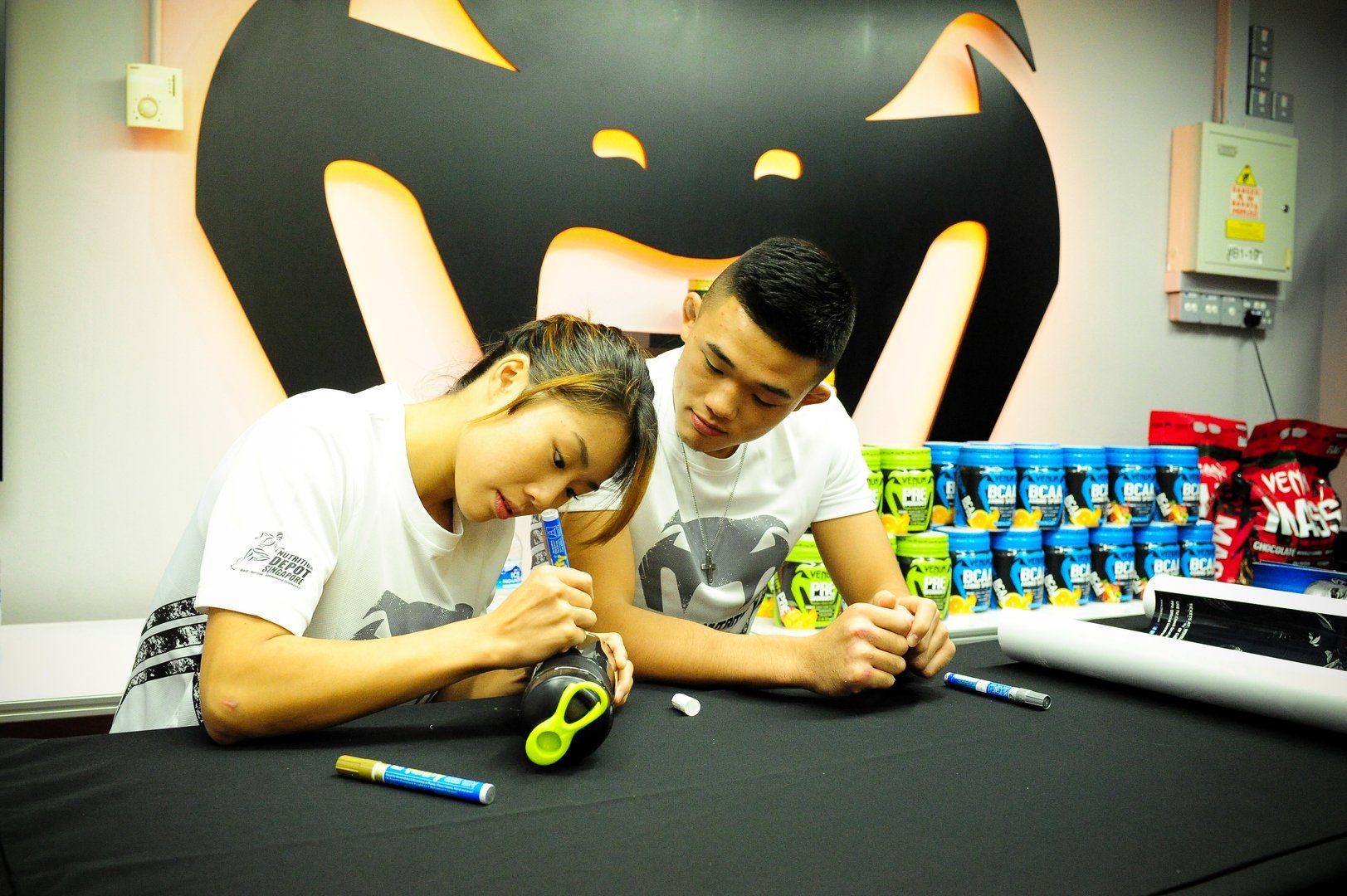 Angela and Christian sign some merchandise at a meet & greet event with their fans.