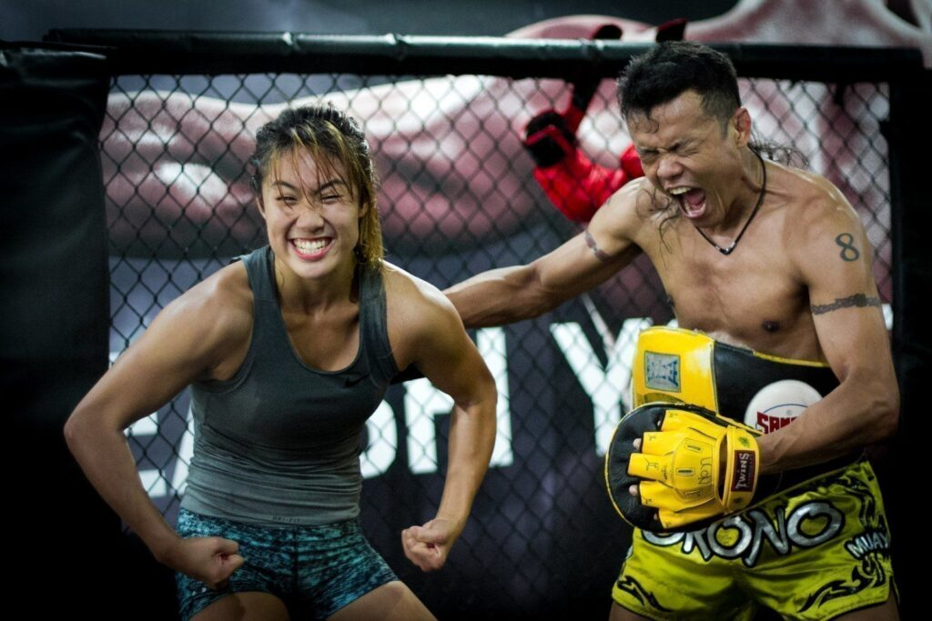 ONE Women's Atomweight World Champion Angela Lee strikes a pose with her coach, multiple-time Muay Thai World Champion Orono Wor Petchpun.