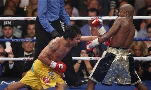 Manny Pacquiao, from the Philippines, left, lands a body punch to Floyd Mayweather Jr., during their welterweight title fight on Saturday, May 2, 2015 in Las Vegas. (AP Photo/Eric Jamison)
