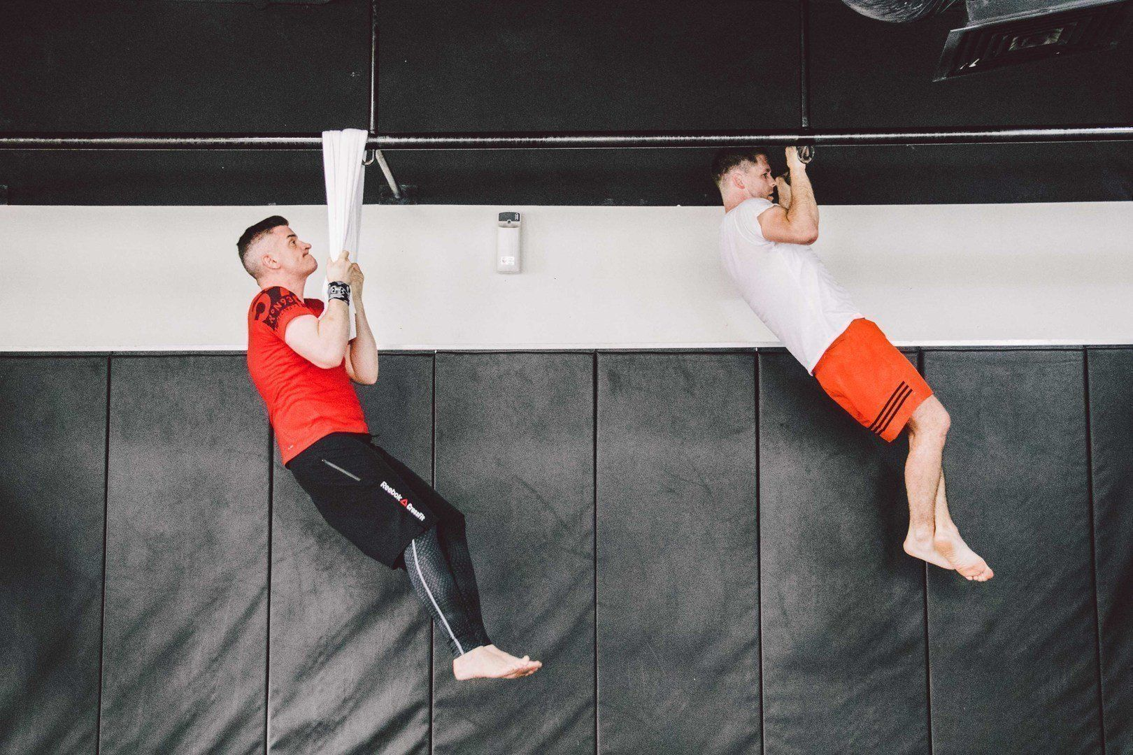 two people doing pull-ups