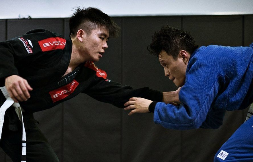 Two BJJ practitioners sparring.