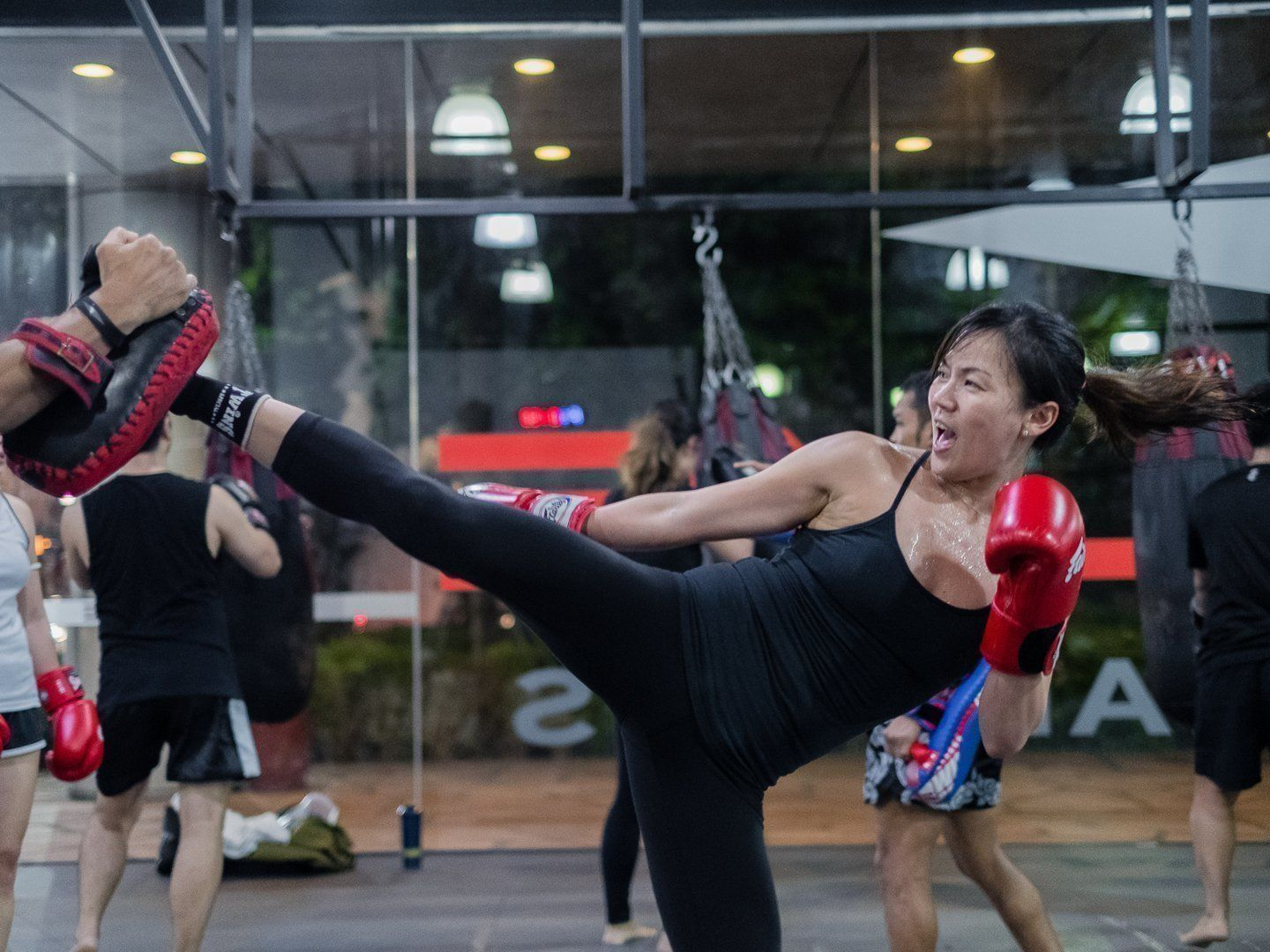 A woman throws a Muay Thai head kick during training.