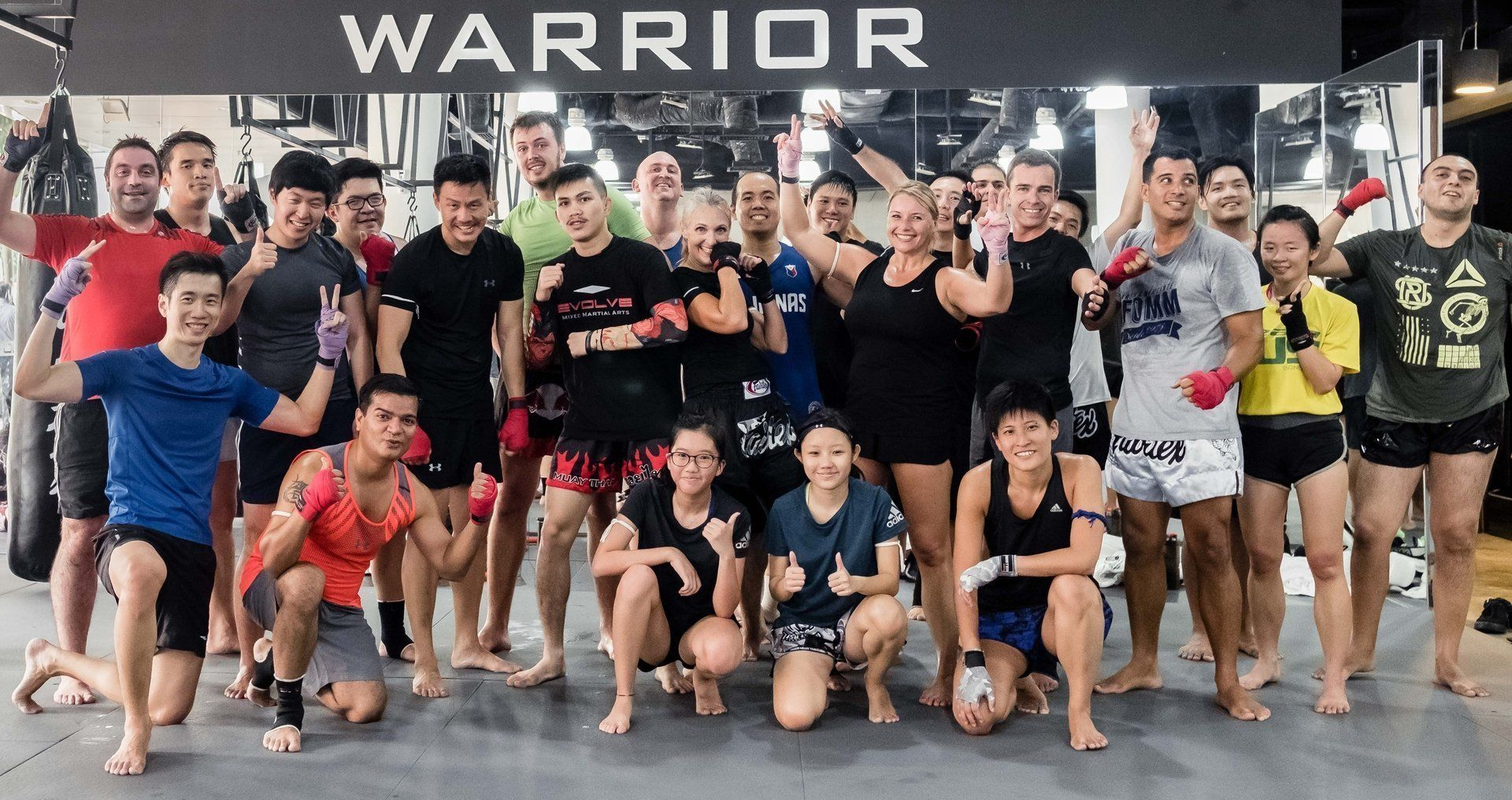 A group of Muay Thai students smiling after class.