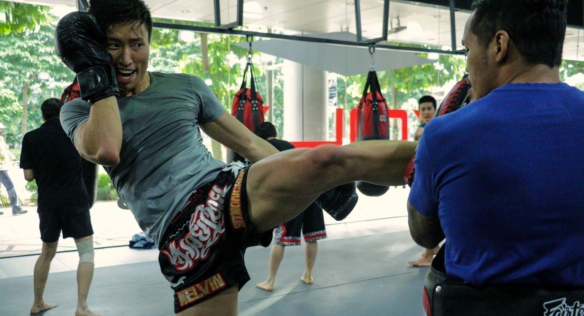 A Muay Thai student throws a kick at the pads during a class.
