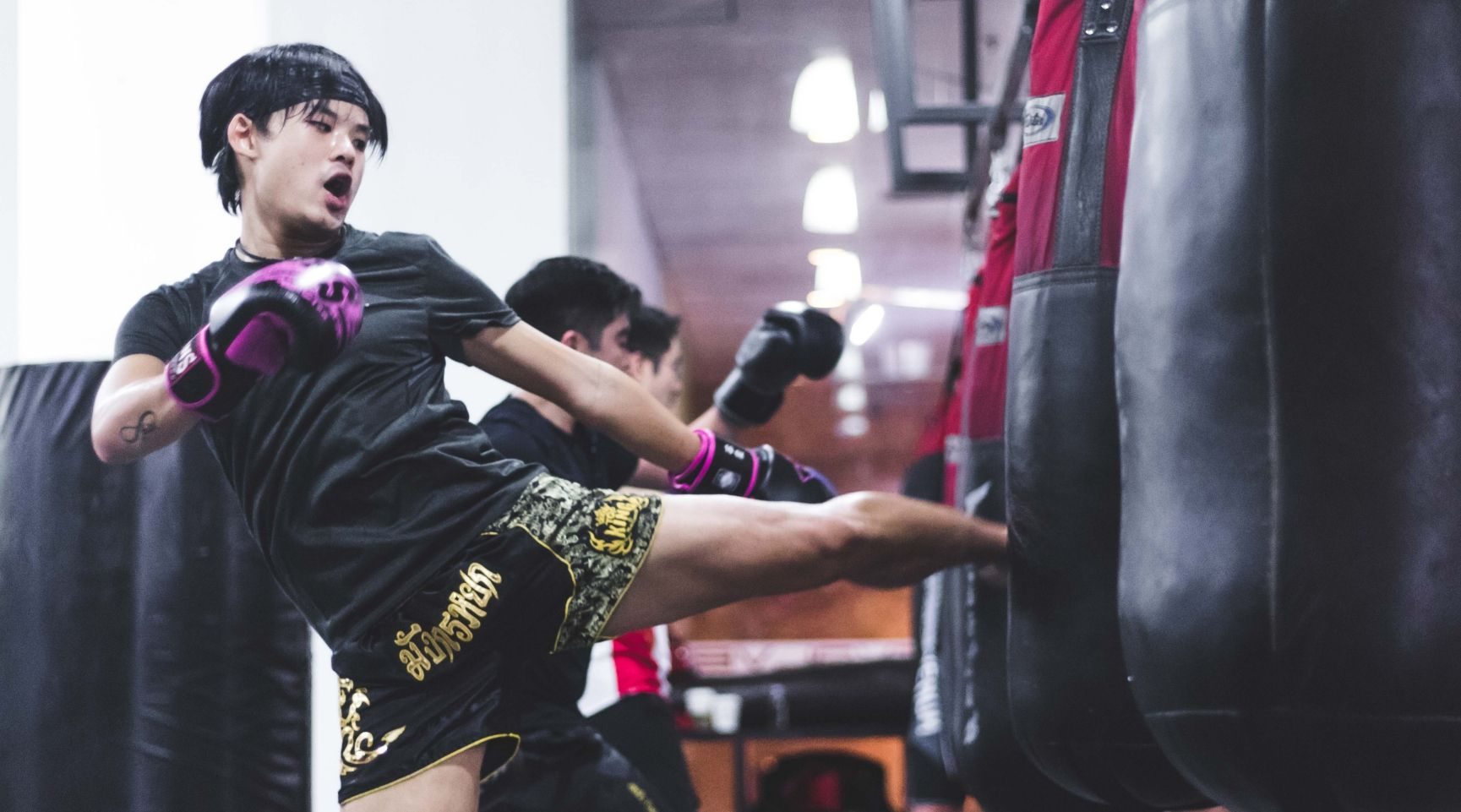 A Muay Thai student throws a left kick at a heavy bag during a Muay Thai class.