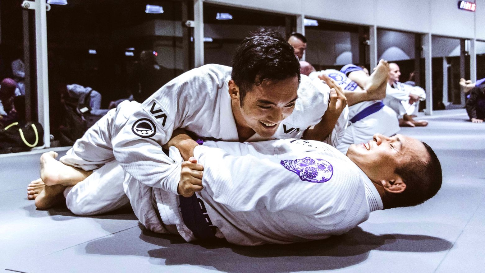 Two people smiling while training BJJ