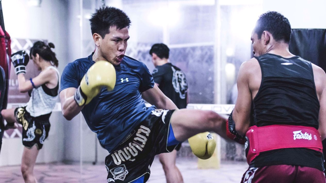 A student kicks the pads during a Muay Thai class at Evolve MMA (Far East Square) in Singapore.