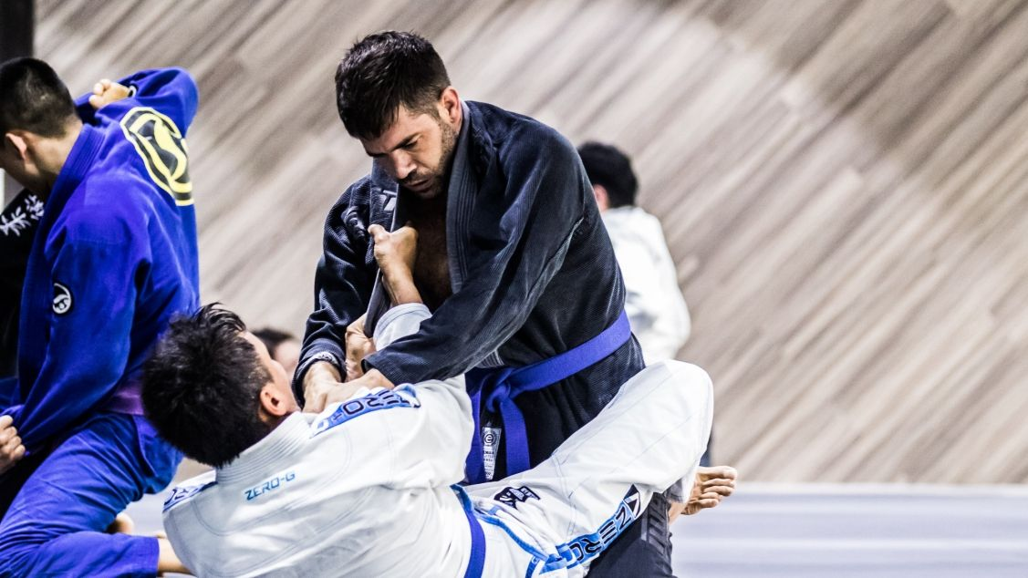 Two BJJ students sparring in class