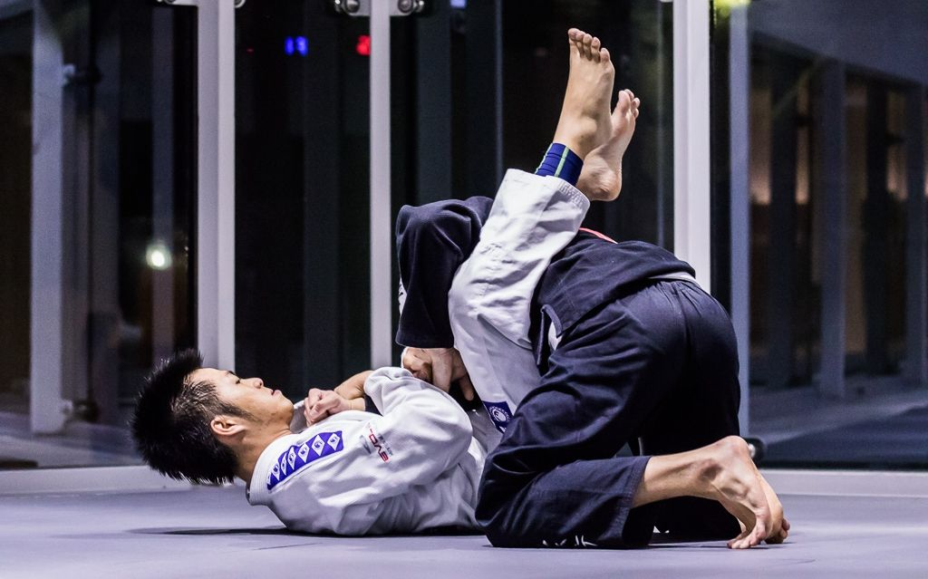 Two BJJ students rolling on the mats.