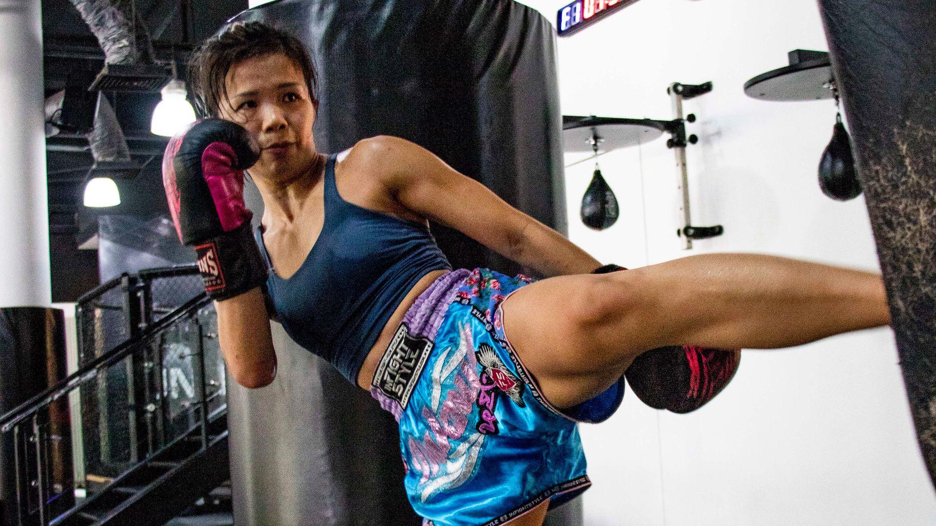 A female Muay Thai fighter kicks a bag at the gym.