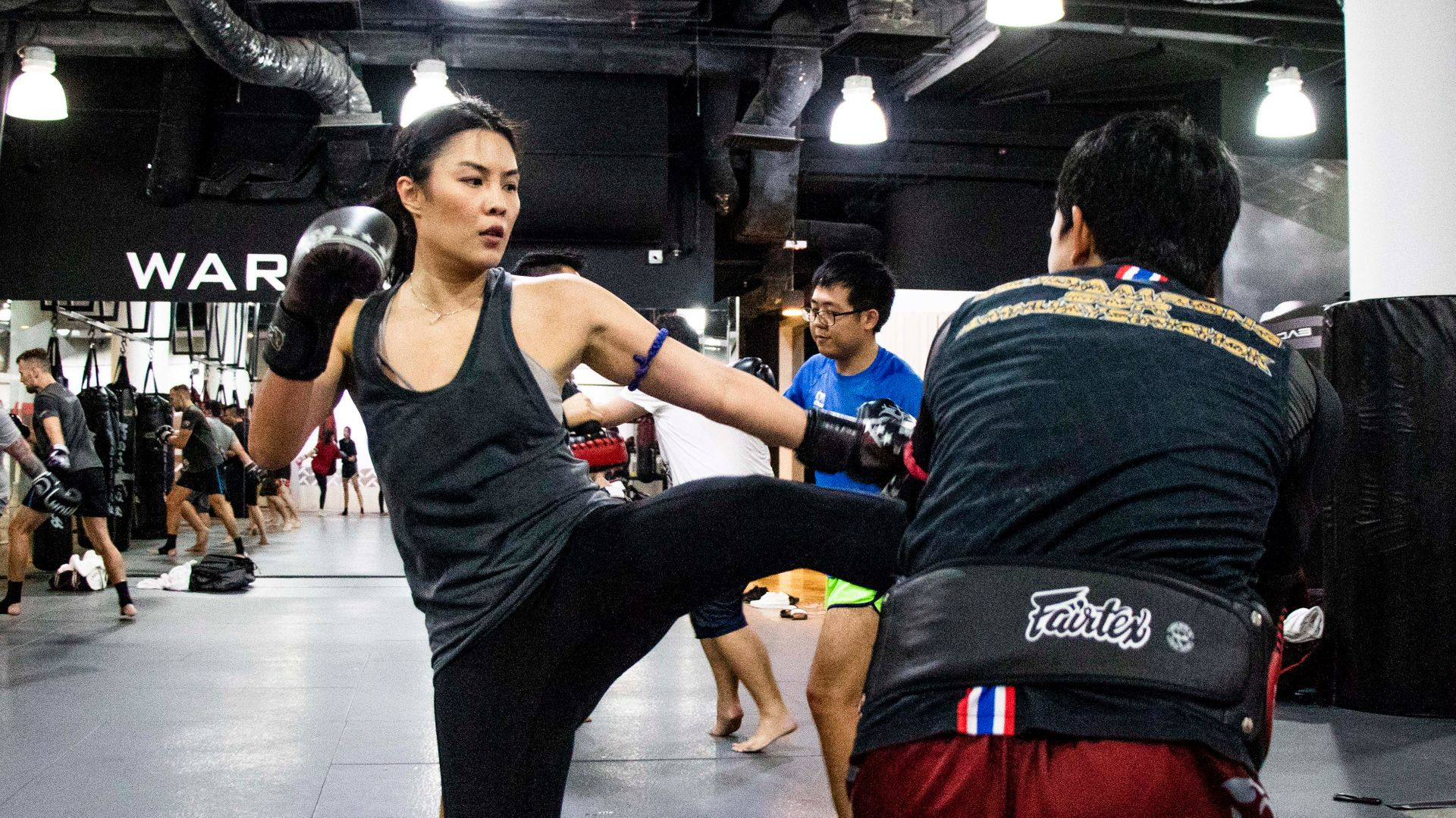 A female Muay Thai students throws a kick in class