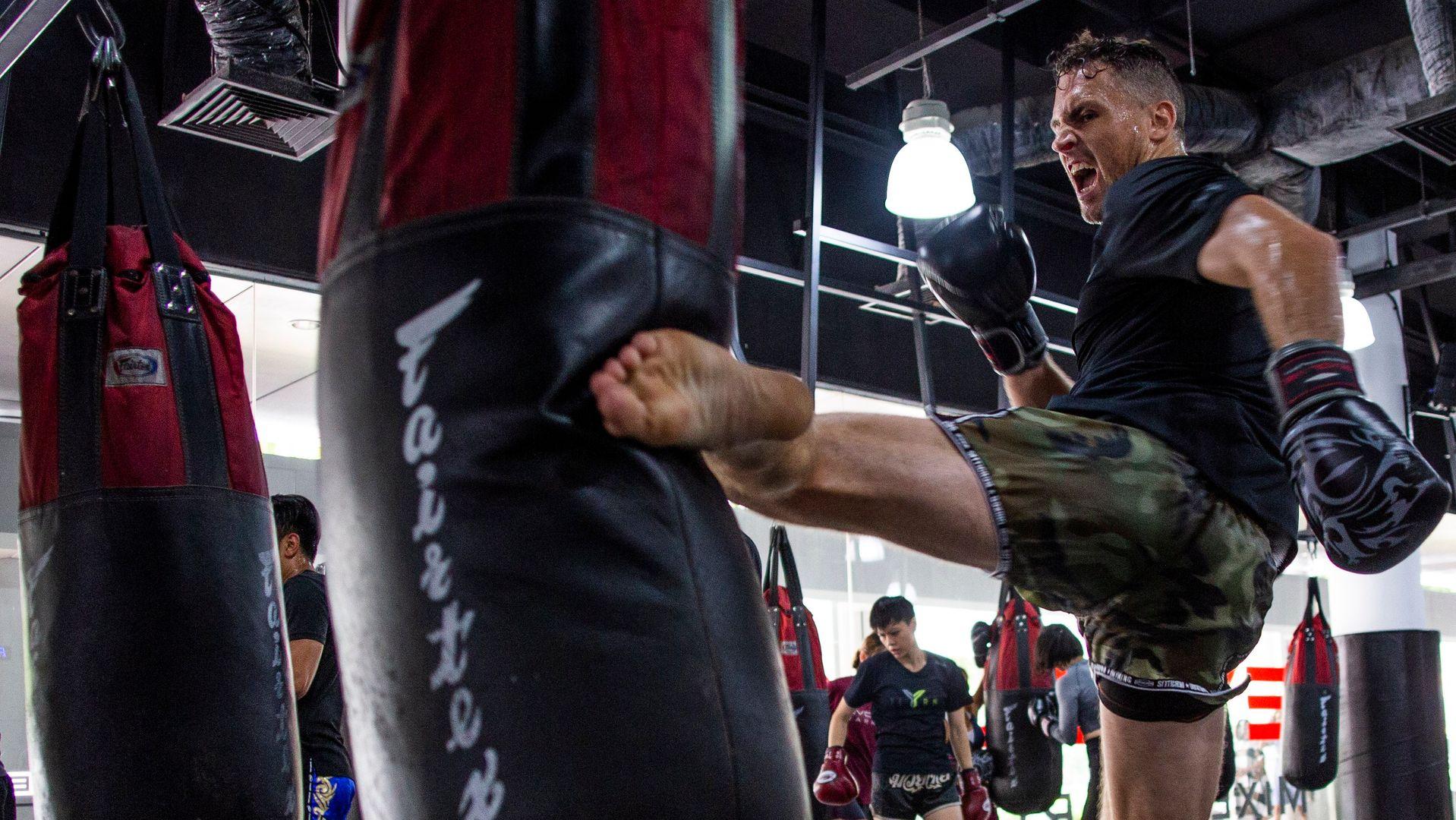 A man throws a Muay Thai kick on a heavy bag.