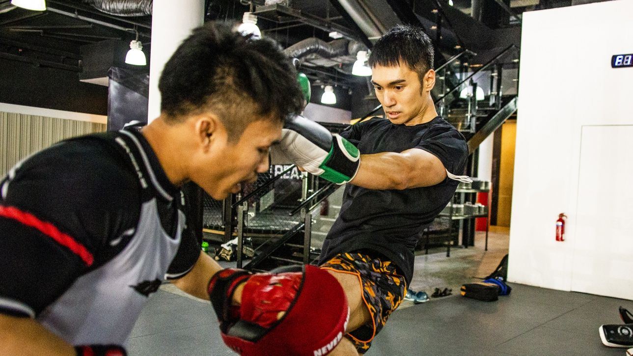 A Muay Thai fighter throwing a knee at the pads.