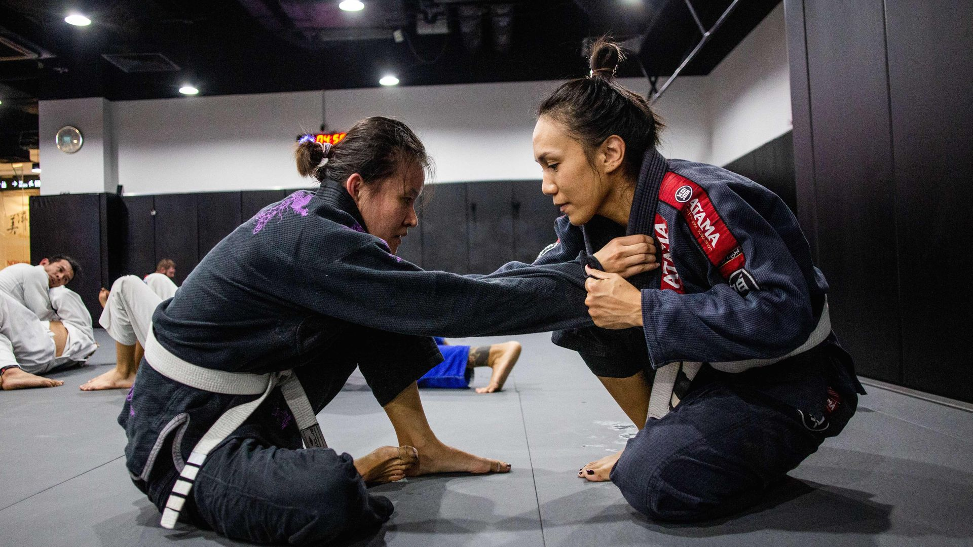Two people sparring in BJJ class.