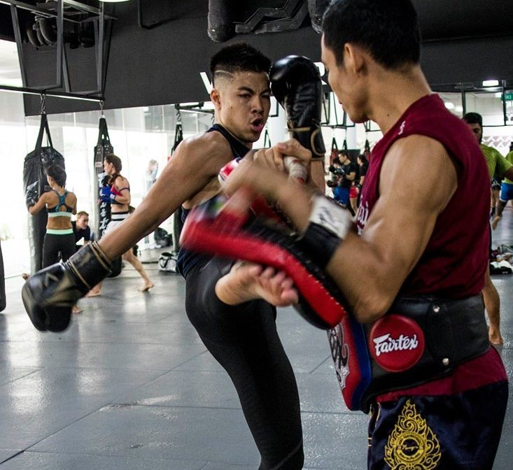 A Muay Thai student throws a kick during a class