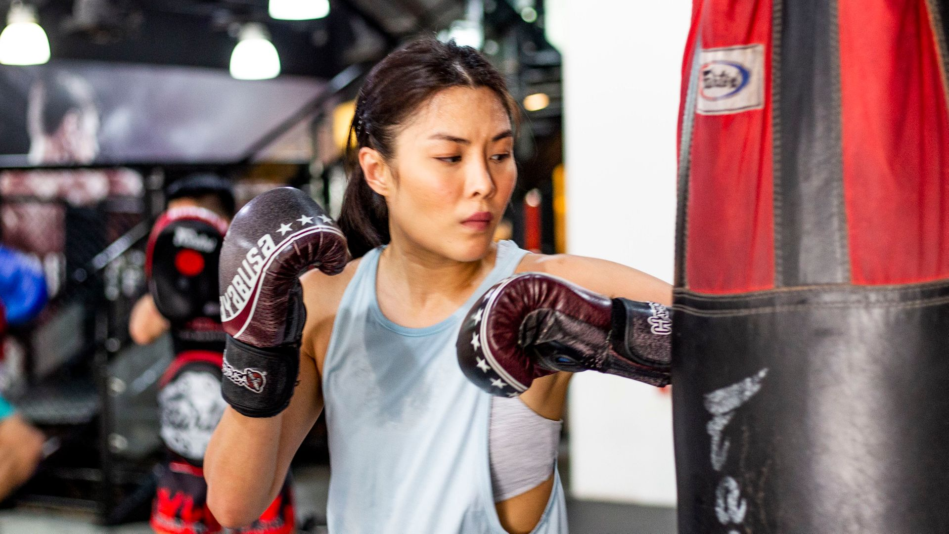 A female Muay Thai student throwing an elbow on a heavy bag.