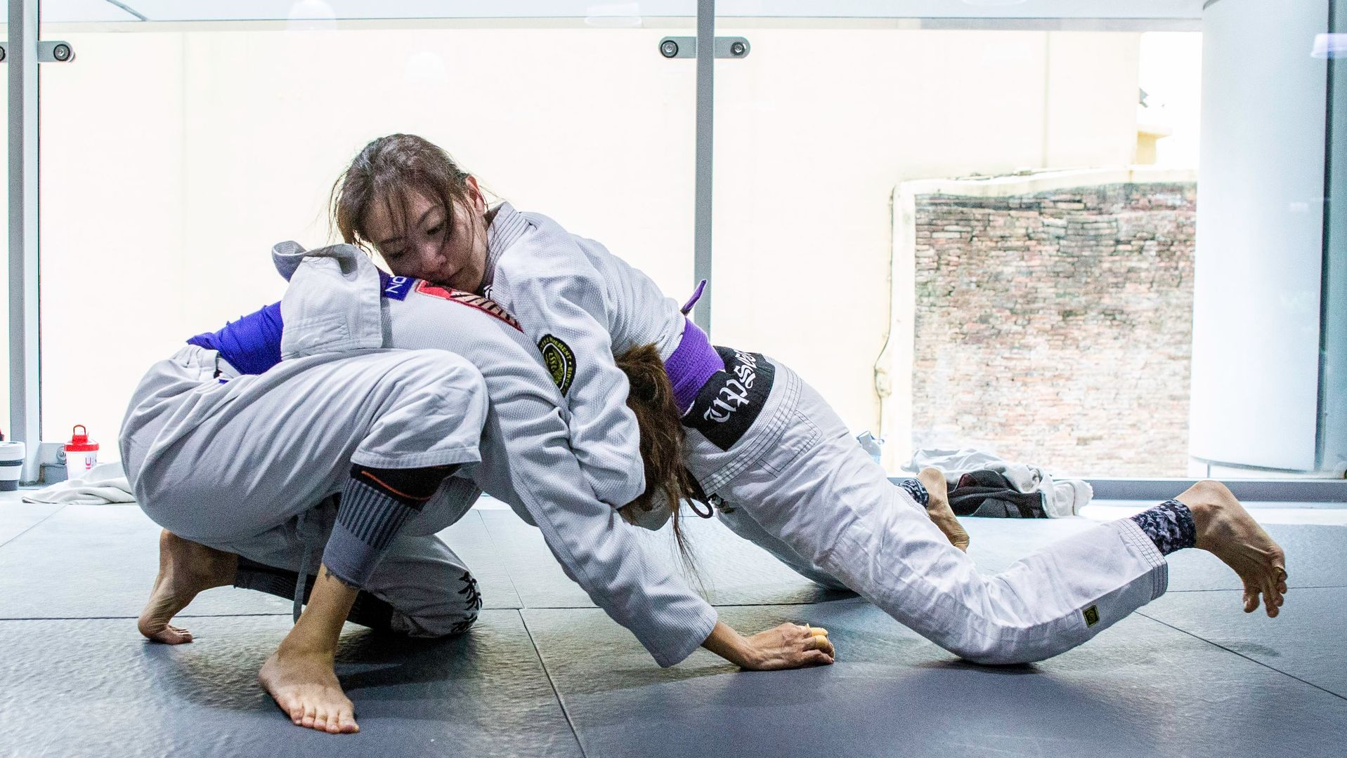 A student doing a front headlock in BJJ class.