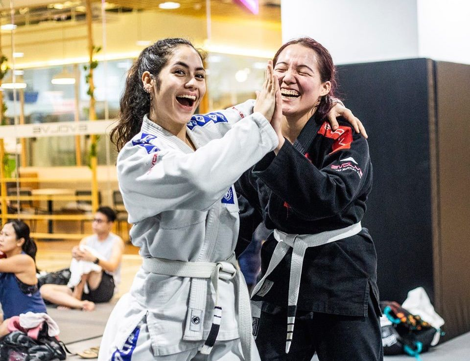 Two BJJ students wearing gis laughing.