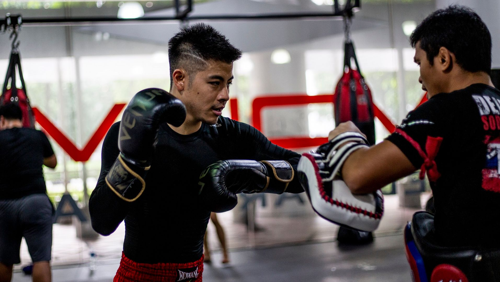 A Muay Thai student throws an elbow at a pad