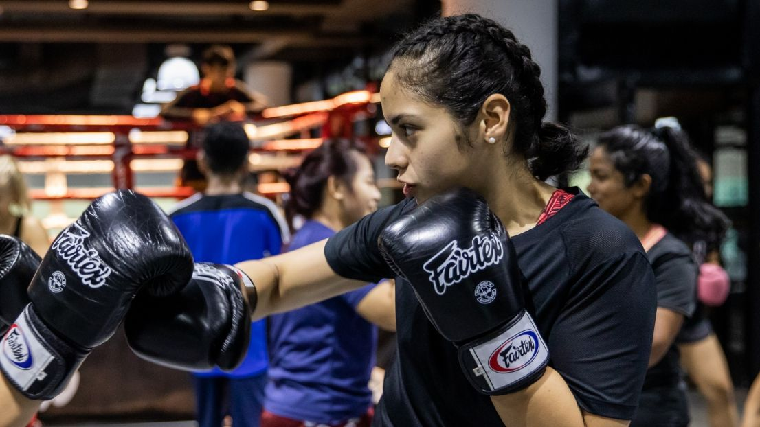 A female boxer throwing a hook punch during a Muay Thai class.