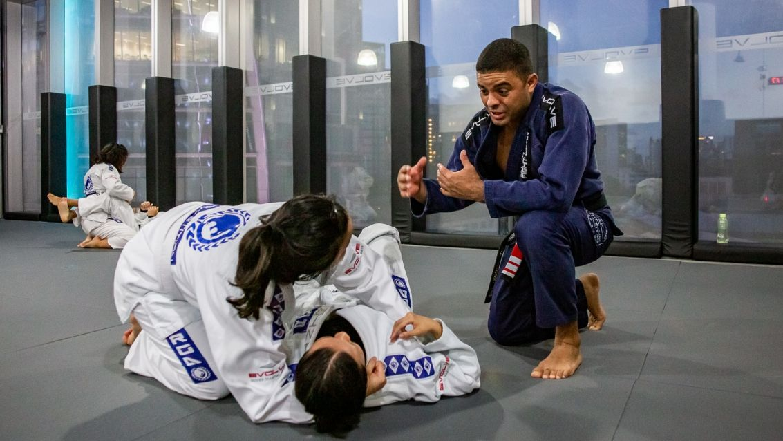 A BJJ professor teaching two students in class.