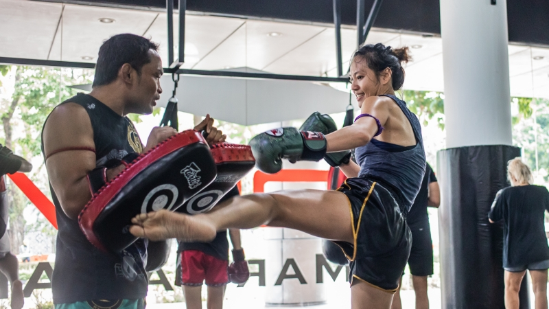 female kicking muay thai pads
